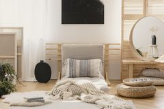 White warm blanket and patterned pillow on beige futon in stylish natural bedroom interior with elegant round mirror in wooden. Frame on table, real photo with stock images