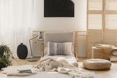White warm blanket and patterned pillow on beige futon in stylish natural bedroom interior, real photo with mockup on the empty. Wall royalty free stock photo