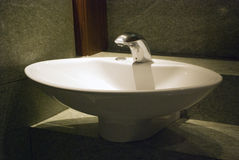White wash basin with tap and lighting Stock Photography