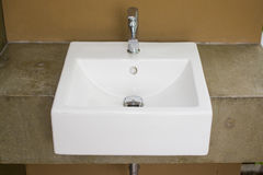 White washbasin with color earth tone. Of cement Royalty Free Stock Photography