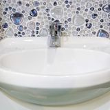 White washbasin faience and chrome plumbing faucet in the bathro. Om Royalty Free Stock Photos