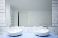 Mirror in simple bathroom interior. White washbasins against brick wall with mirror in simple bathroom interior royalty free stock photography