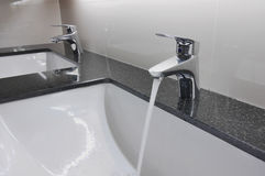White washbasins and faucet on granite counter Stock Photography
