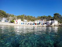Mediterranean colourful town from the water. White washed buildings with colourful windows and doors view from the boat across the water royalty free stock photos