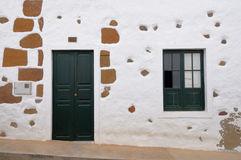 White-washed house in Haria, Lanzarote, Canaries. Dark green window and a door on a white-washed façade of an old house in Haria, Lanzarote, Canary Islands Stock Image