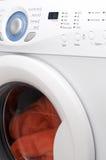 White washing machine. With orange towels inside Stock Image
