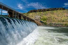 White water flows over Diversion Dam on the Boise River in the spring. High water flows at a high velocity through a diversion dam in Idaho royalty free stock photography