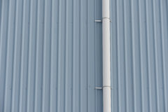 White water pipe on gray wall. Plastic white rain water pipe attached to tall wall made of gray painted corrugated sheet metal Royalty Free Stock Image