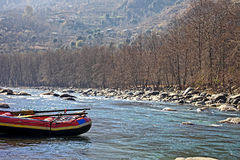 White Water Rafting Boat in Indian River. Anchored white water rafting boat in the Himalayas at the Beas river in Manali, India Royalty Free Stock Photos