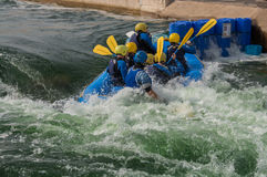 White Water Rafting. A large, rubber raft, holding eight people, entering a river rapid backwards, and taking on water Royalty Free Stock Photos