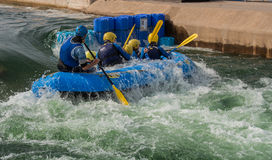 White Water Rafting. A large, rubber raft, holding eight people, entering a river rapid backwards, and taking on water Stock Photos