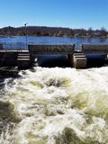 Spring water raging through Locks on Trent River. White water raging through the locks from the tranquil blue water of the river above the dam royalty free stock photography