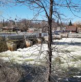 Spring water raging through Locks on Trent River. White water raging through the locks from the tranquil blue water of the river above the dam stock photography