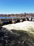 Spring water raging through Locks on Trent River. White water raging through the locks from the tranquil blue water of the river above the dam stock photos