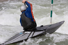 White Water Slalom. A canoeist paddling through fast running white water - about to go down a drop Stock Images