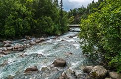 The Susitna River Runs Wild Through the Forest North of Palmer, Alaska. The white waters of the Susitna Run under a bridge north of Palmer, Alaska Stock Photo