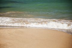 White wave of the azure sea is washed by the sandy beach, copy spase stock images