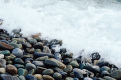 White wave washing the stones of the shore. Background with beach of stone. stock photos