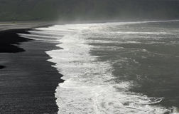 White waves on black beach. The beach with black volcanic sand  beaten  by white waves is at Dyrhólaeyjarviti in the south of Iceland Royalty Free Stock Photos