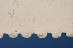 White wavy empty wall in blue sky with copy space. Creative background of detail part of white wavy roof building in blue sky, algarve, portugal Stock Photo