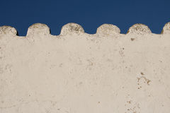 White wavy empty wall in blue sky with copy space. Creative background of detail part of white wavy roof building in blue sky, algarve, portugal Royalty Free Stock Image