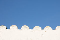 White wavy empty wall in blue sky with copy space. Creative background of detail part of white wavy roof building in blue sky, algarve, portugal Stock Photos