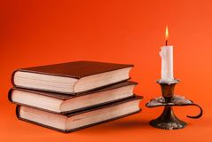 Candle burning in candlestick and three old books  on orange background Royalty Free Stock Photo