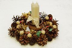 White wax candles tied with openwork ribbon and a Christmas wreath of cones, walnuts, chestnut fruits on white concrete background stock photo