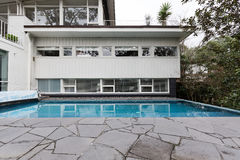 White weatherboard mid centurynhome with in ground swimming pool. And crazy paving Stock Images