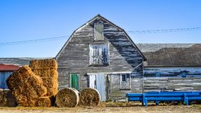 White Weathered Barn with Haybales Stock Photo