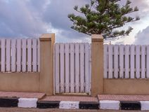 White weathered wooden garden gate and fence with background of single tree and cloudy sky at sunrise time. White weathered wooden garden gate and fence with royalty free stock photography