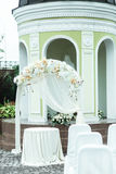 White wedding altar stands on the backyard behind an old chapel Stock Photos