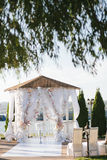 White wedding arch arbor decorated with white flowers. And cloth, chairs, on the river bank Stock Image