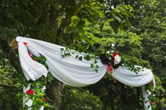 White Wedding Arch In Nature. Wedding arch wrapped in a white cloth and vines. The arch is surrounded by trees and bushes Stock Images