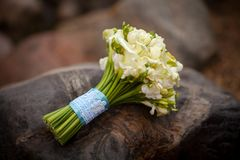 White wedding bouquet with blue ribbon. Lying on the stone Stock Images
