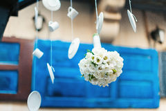 White wedding bouquet hanging upside down. On a background of blue doors and white kitchen ware. unique photo Stock Photography