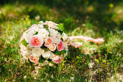 White wedding bouquet lying on green grass Stock Photo