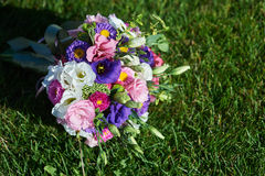 White wedding bouquet lying on green grass Royalty Free Stock Image