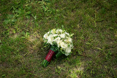 White wedding bouquet with roses and chamomile lies on a grass Stock Photos