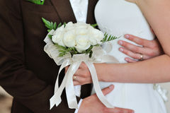White wedding bouquet of roses in hands of the bride and groom.  Stock Images