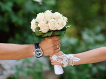 White wedding bouquet of roses in hands of the bride and groom. Royalty Free Stock Photo