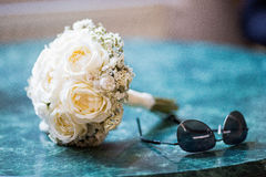 White wedding bouquet with sunglasses on a blue marble table. White wedding bouquet with aviator style black sunglasses on a blue marble table Royalty Free Stock Photos
