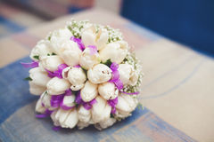 White wedding bouquet of tulips with purple ribbon on sofa. Beautiful white wedding bouquet of tulips with purple ribbon on sofa Royalty Free Stock Images