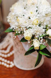 White wedding bouquet in a vase on the table.  Stock Photos