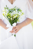 White wedding bouquet. Young bride in dress with decollete holding in hands wedding bouquet made with white blossoms, close up, focus on flowers Stock Image
