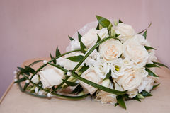 White wedding Bridal bouquet of cream roses, bound with grass,  pearly beads on light background Stock Photo