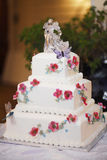 White wedding cake. A view of a three-layered white wedding cake with decorative red flowers and a bride and groom ice or clear plastic sculpture on the top Stock Image
