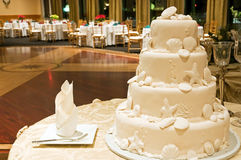 White wedding cake. A view with an all white multi-layer wedding cake with seashell decorations in the foreground and banquet tables in the background Royalty Free Stock Image