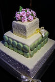 White Wedding Cake. Classic 3 tier white wedding cake with purple flowers and ribbon. Stock Images