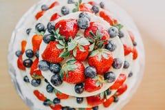 white wedding cake decorated with cherries, strawberries and blueberries stock photo